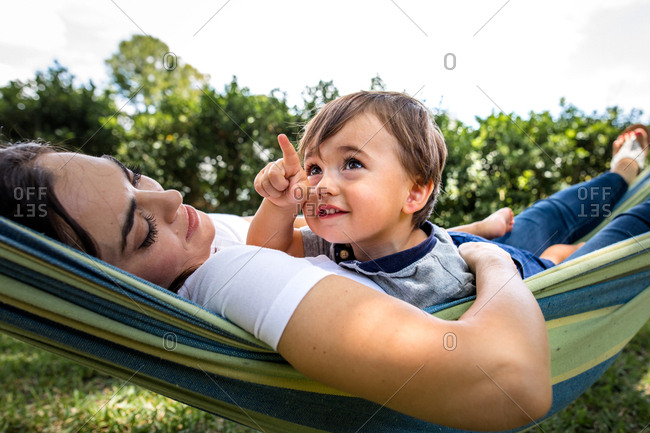Little boy points at something in the distance while laying with mom in a hammock