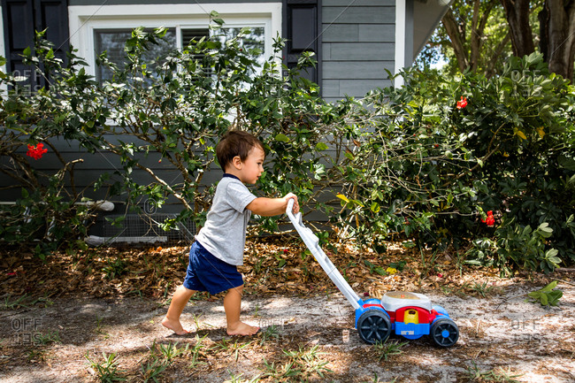Little boy pretends to mow lawn