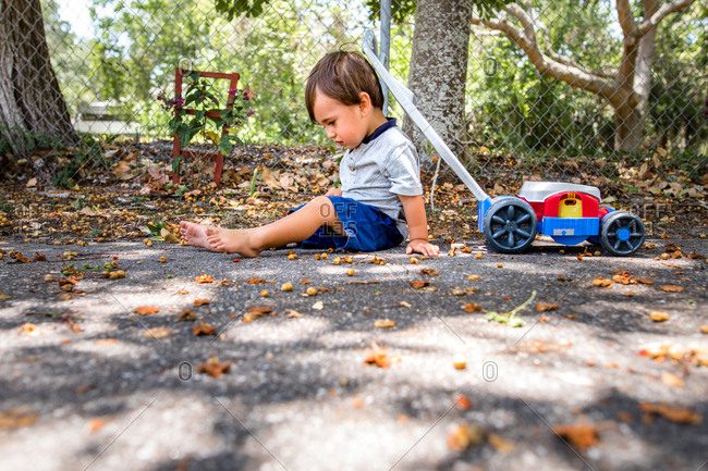 Little boy sits outside with toy lawn mower