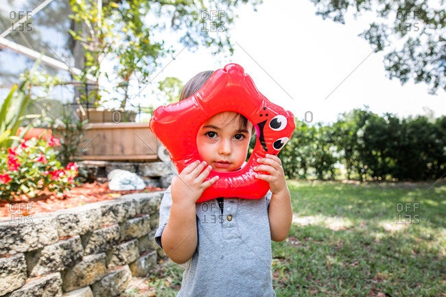 Young boy holding plastic star toy to his face