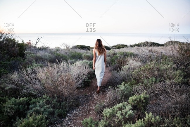 Woman strolling through brush with ocean view