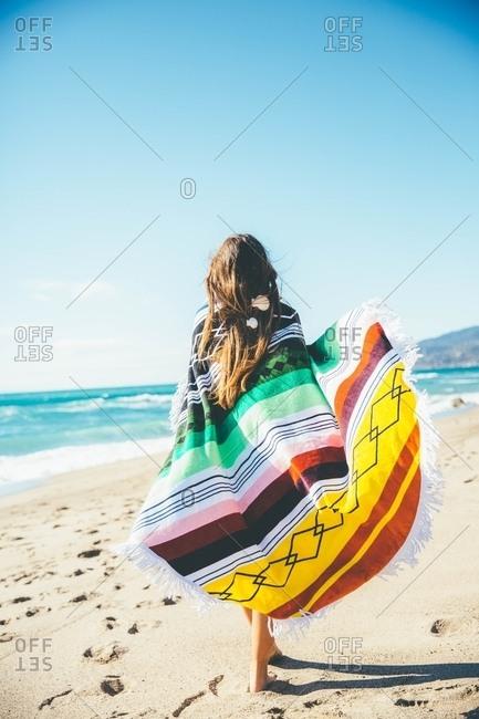 Woman strolling beach wrapped in blanket