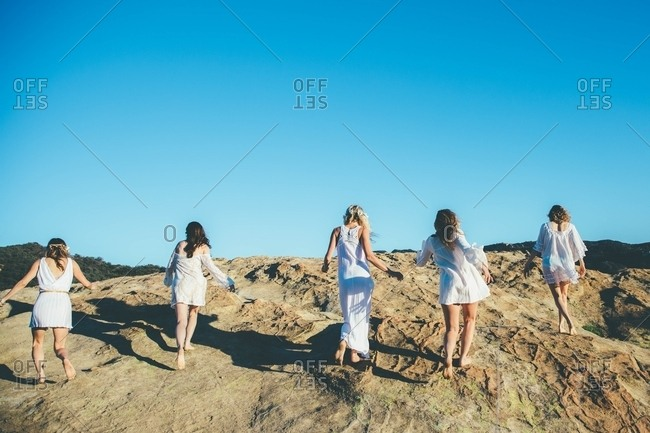 Women in white walking in sand dunes