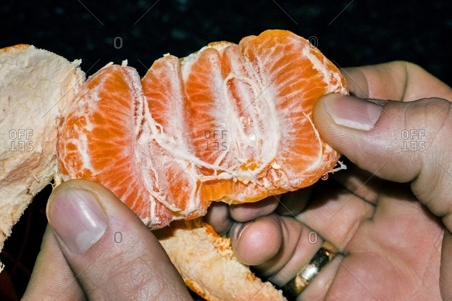 Hand opening up an orange