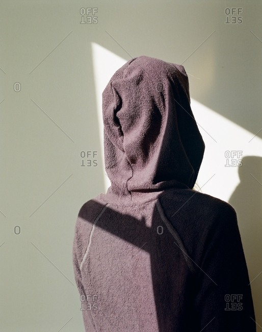 Person in hoodie facing sunlit wall