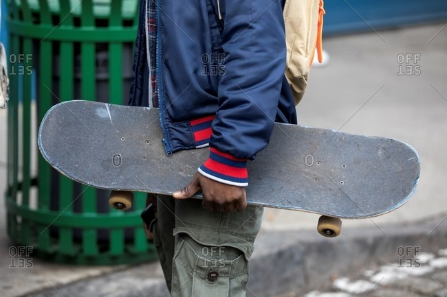 Young man carrying skateboard down city street