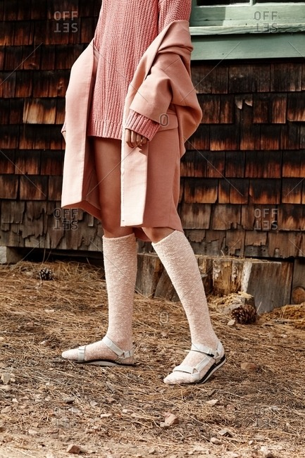 Woman wearing pink sweater and tall socks with sandals