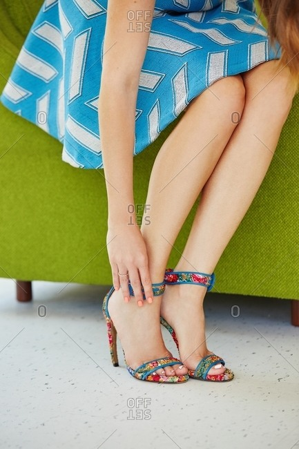 Woman adjusting strap of her sandals