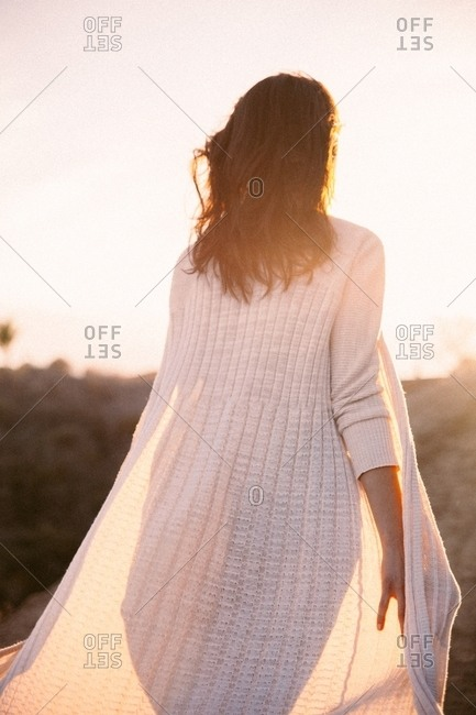 Rear view of a brunette woman wearing white sweater walking in sunset light