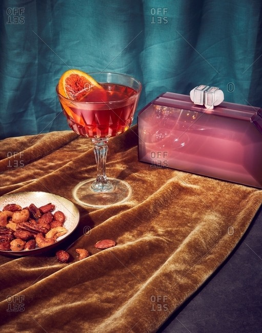 Mixed nuts served with a cocktail by purple clutch