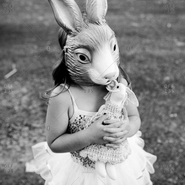 Little girl in rabbit mask holding  a stuffed rabbit
