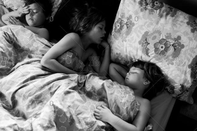 Three children asleep in bed