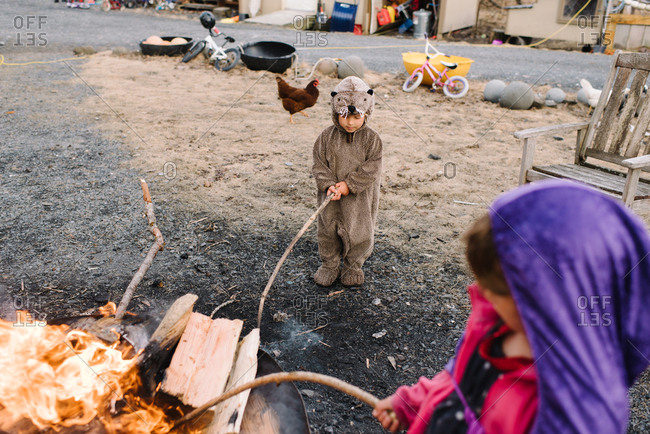 Children in costumes playing around fire pit