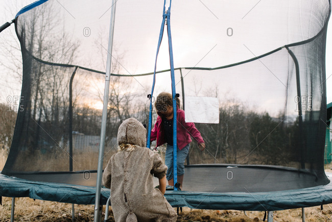 Child in animal costume joining girl on trampoline