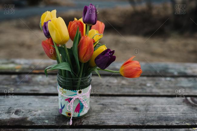 Vase of yellow, purple, and orange tulips