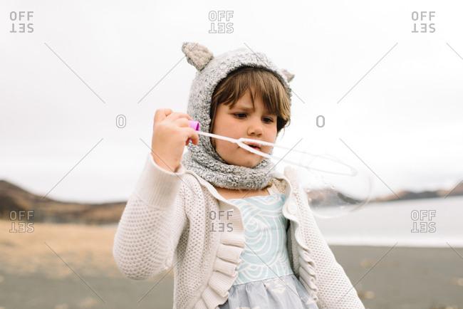 Little girl in knit hat with ears blowing bubbles