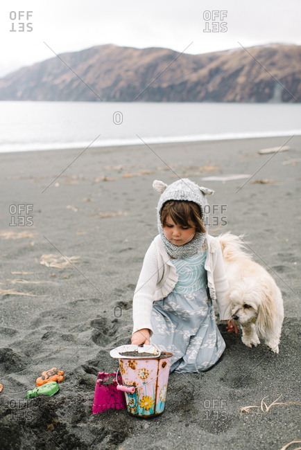 Little girl with dog playing on beach