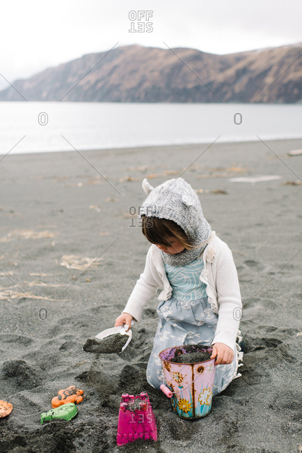 Girl in knitted hat and dress digging in sand
