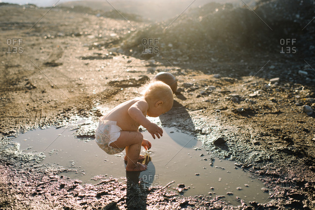 Baby in diaper playing in mud puddle