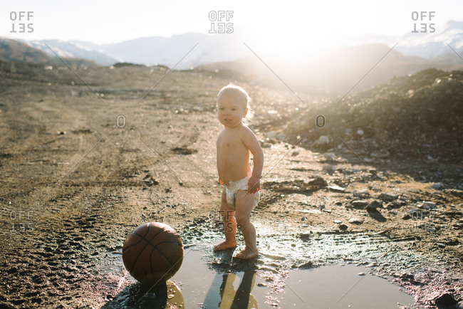 Baby in diaper with ball in mud puddle