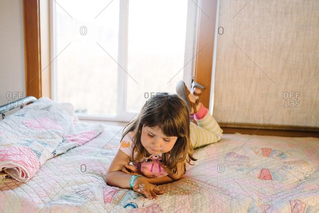 Preschool aged girl lying on bed