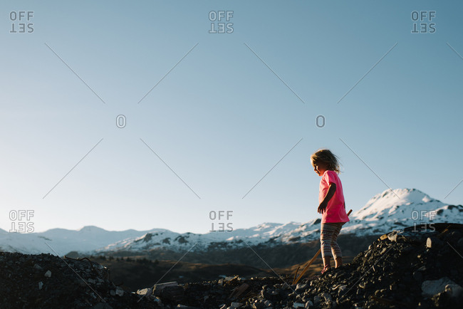 Child standing on pile of rocks with mountains in distance