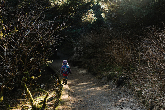 Child in hooded coat walking on trail