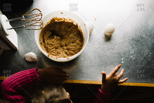Child at kitchen counter with bowl of batter