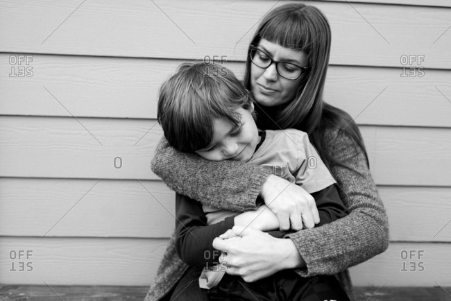 Young boy enjoys hug from his mother