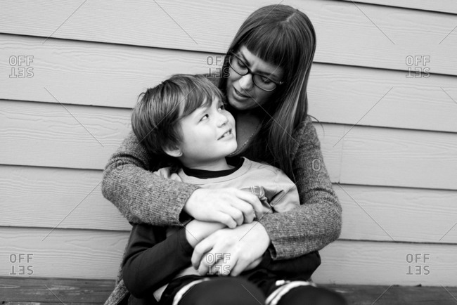 Woman talking to her son while holding him on her lap