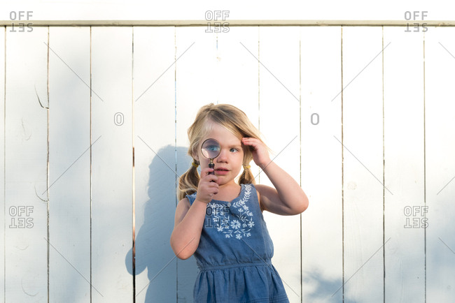 Little girl standing in front of a fence peering through a magnifying glass