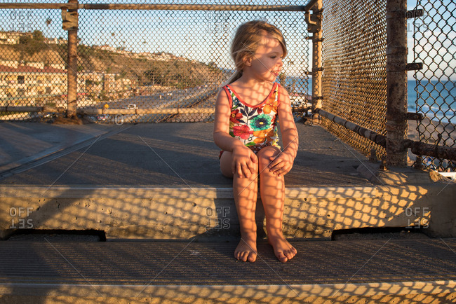 Little girl sitting on steps at a beach access overlooking the ocean