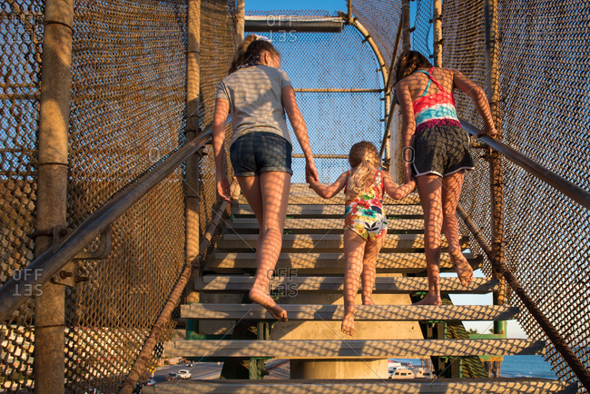 Three sisters holding hands walking up steps at a beach access