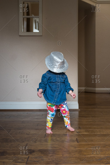 Little girl playing with an oversized silver hat on her head