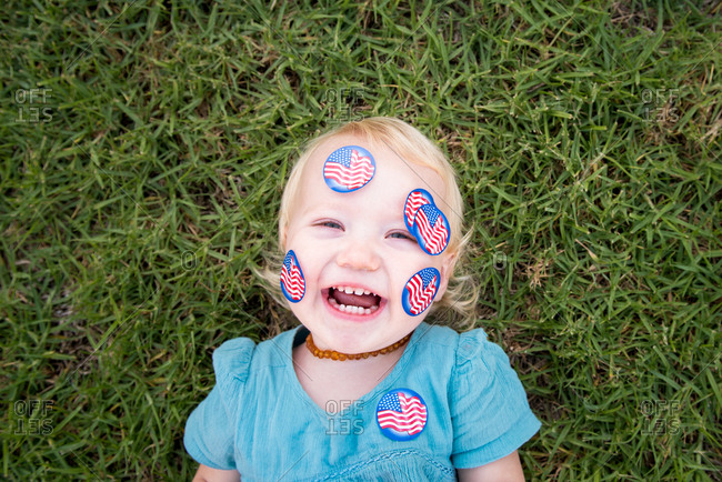 Toddler girl lying in the grass with american flag stickers on her face
