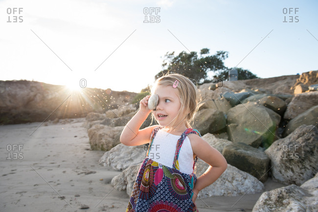 Little girl covering her eye with a shell on a beach