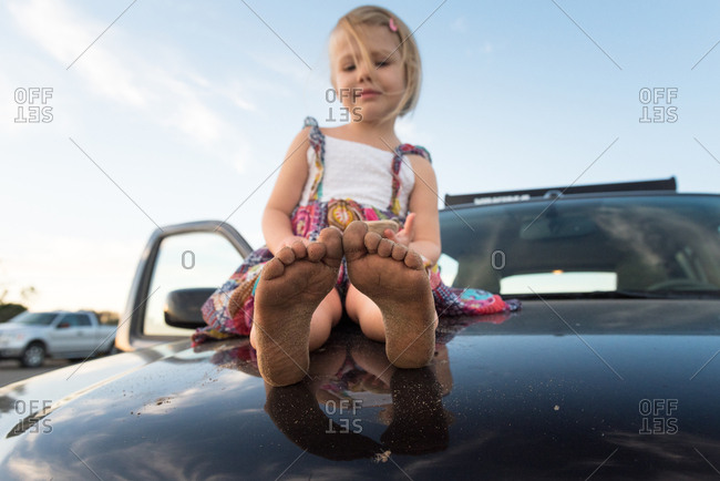 Little girl with sandy feet sitting on the hood of a car