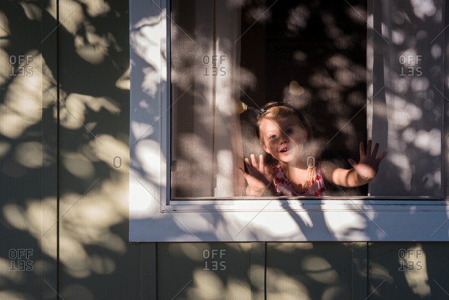 Little girl looking through a window screen smiling