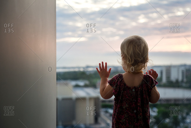 Toddler girl standing at a window overlooking a city