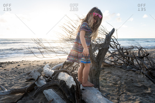 Girl walking on a piece of driftwood on a beach at sunset