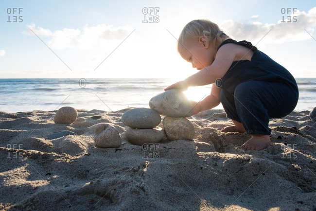 Toddler girl stacking stones on a beach at sunset