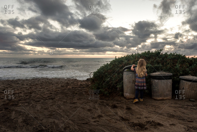 Little girl putting trash in a can on a beach at sunset