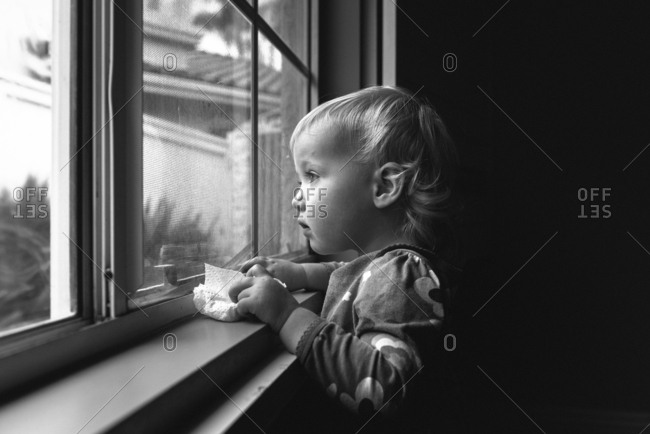 Toddler girl with a paper napkin looking out a window