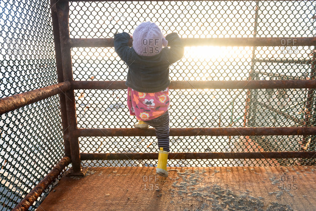 Little girl climbing on a rusted railing at a beach access point