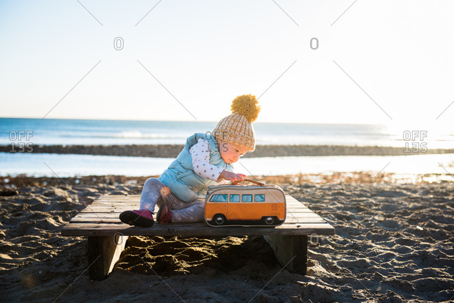 Toddler girl sitting on a wooden platform with a lunch box on a beach