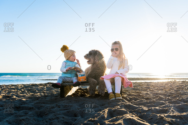 Two girls sitting on a beach platform with a labradoodle at sunset