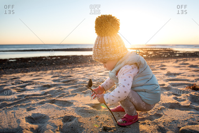 Toddler girl in a toboggan playing on a beach at sunset