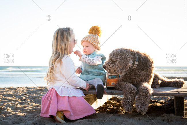 Two sisters eating a snack with their labradoodle on a platform on a beach