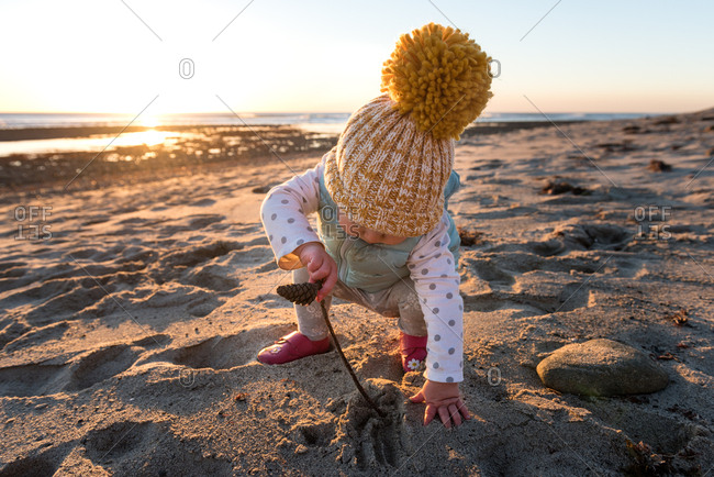 Toddler girl in a toboggan playing with a stick on the beach
