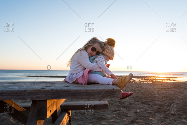 Girl sitting on a picnic table at a beach holding her toddler sister in her lap